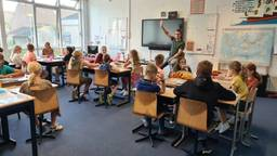 Vrolijk beginnen kinderen aan nieuw schooljaar in gebouw dat minder fris is