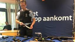 De Koninklijke Marechaussee toont in beslag genomen (nep)wapens.