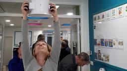 Froukje meet de hoeveelheid lucht door een ventilatierooster in een school. (Foto: Froukje van Dijken)