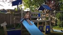 Joris (5) geniet van de zelfgemaakte waterglijbaan (privéfoto).