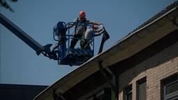 Met een hoogwerker wordt een dak aan de Biezenloop gerepareerd.