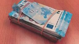 Onder de bijrijdersstoel lagen twee pakken met geld (foto: Koninklijke Marechaussee).