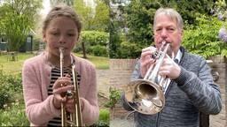 Lize en Harmen met hun trompet in de tuin (foto: Jan Peels).