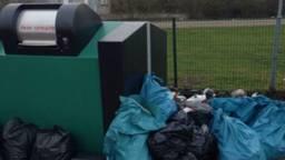 Schippers dumpen hun afval naast de afgesloten afvalbak