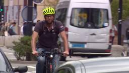 Het is een apart straatbeeld: een fietser tussen de auto's en vrachtwagens.