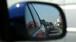 Een file gezien vanuit een zijspiegel van een auto.