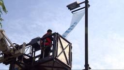 Een van de banners wordt opgehangen.