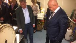 De minister bekijkt een draaiende pillenmachine