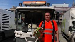 Een van de schoonmakers van ERGON met een bosje bloemen en PSV sjaal als dank