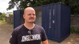 Initiatiefnemer Vic van Dijk naast de hangcontainer