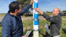 Boeren hangen flyers op in verschillende talen om te waarschuwen tegen varkenspest