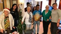 De kinderen met wat ouderen, wethouder Marianne de Bie en de kerstboom