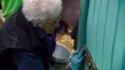 Miep Verburg druk bezig met het schilderen van details