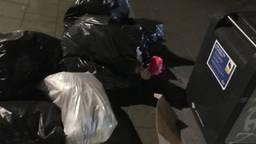 Volle afvalzakken naast een container. (Foto: Fleur Besters)