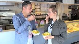 Verslaggever Ronald Sträter eet een frietje met FOX-presentatrice Hélène Henriks.