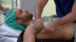 De patiënt/verslaggever ligt op een matje en krijgt kussens op zijn buik geplakt. (foto: Omroep Brabant)
