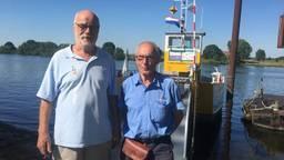 Frans van Tiel (links) en Guus van Uden (rechts) genieten op hun pontje Vice Versa.