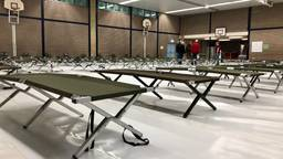 Vrijwilligers zetten maandag tientallen veldbedden in de gymzaal van scholengemeenschap 't Rijks. (Foto: Erik Peeters)