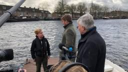 De Koning praat met Max van Zon die afval uit het water haalt met zijn bootje (Foto:Tom van den Oetelaar)