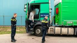 De gewonde trucker pakt zijn spullen uit de cabine. (Foto: Marcel van Dorst/SQ Vision)