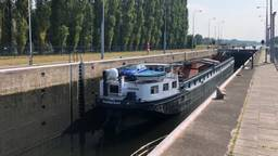 Een boot vaart door de sluis bij Schijndel.