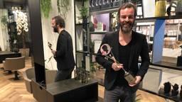 Kapper Arjan Bevers met trofee in zijn lege kapsalon (Foto: Alice van der Plas)