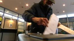 Een stembiljet gaat in de stembus.