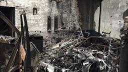De compleet door vuur verwoeste oldtimers in de loods in Vught