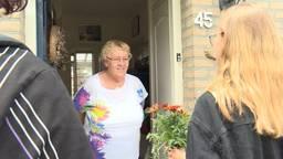 Jongeren verrassen ouderen met een bloemetje.