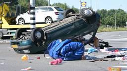 Auto over de kop in Tilburg bij aanrijding, drie gewonden