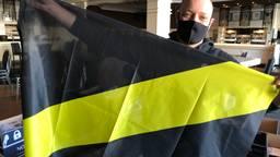 De vereningsvlag van NAC wordt verpakt en verwerkt.