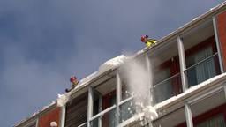 Brandweer haalt gevaarlijk overhangende sneeuw en ijs van dak van winkelcentrum Eindhoven