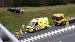 Een auto is naast de A50 een hoog talud opgereden