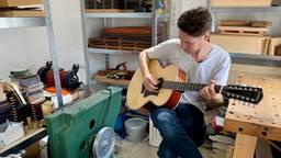Jelle van Tilburg met zijn gitaar in zijn atelier