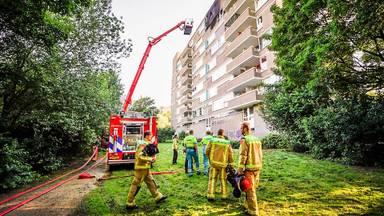 Vanaf een hoogwerker bestrijden brandweerlieden de uitslaande brand op de bovenste verdieping van de flat.