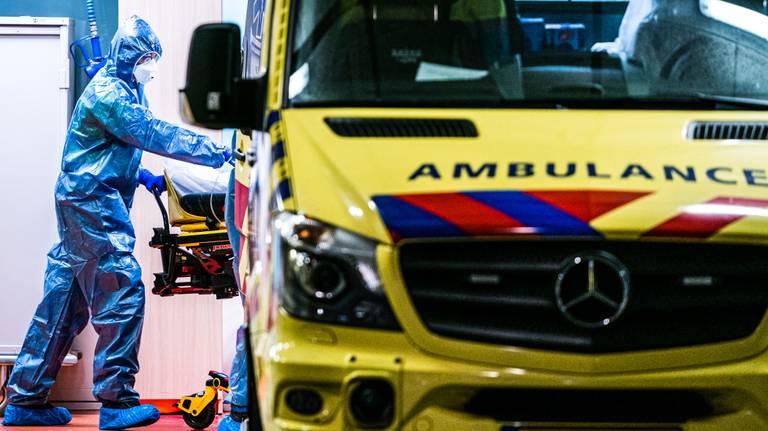 Ziekenhuismedewerkers maken een coronapatient gereed voor herplaatsing vanuit het TweeSteden Ziekenhuis in Tilburg. Foto: ANP
