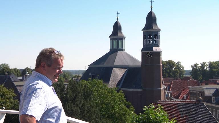 Kees Verhoeckx met op de achtergrond de Sint-Luciakerk.