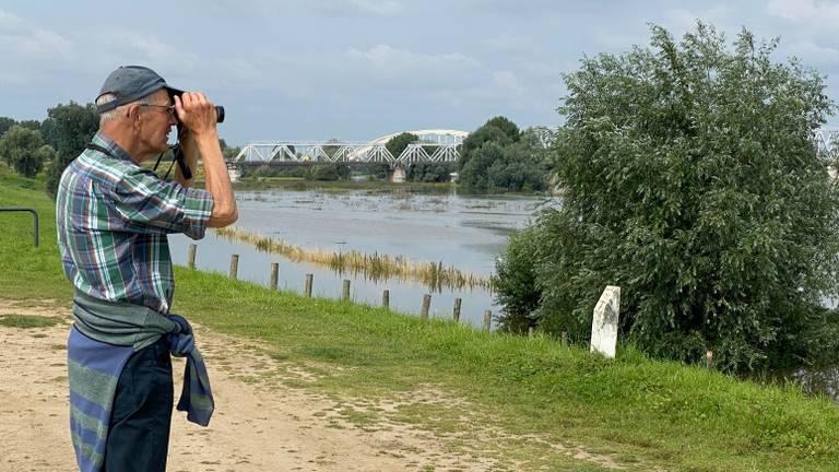 Wandelaar tuurt over de Maas bij Maaspoort in Den Bosch (foto: Jan Peels)