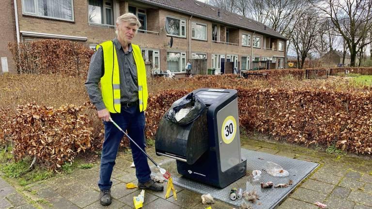 Kees Braam ruim rommel rond de afvalbak in zijn wijk in Eindhoven op (foto: Jan Peels)
