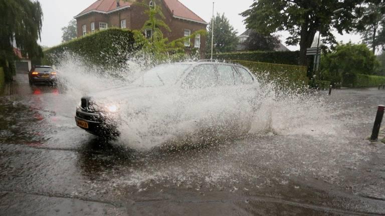 Deze automobilist liet zich niet tegenhouden door het vele water op de Torenstraat in Helvoirt (foto: Bart Meesters).