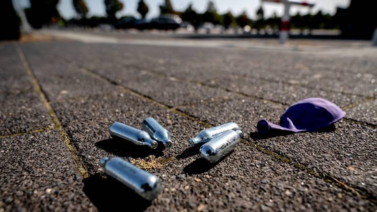 Lachgas patronen en een ballon op een parkeerplaats (Archieffoto: Sander Koning / ANP / Hollandse Hoogte).
