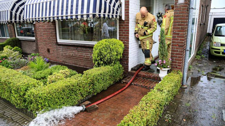 De brandweer pompt water uit een ondergelopen huis (foto: Harrie Grijseels/SQ Vision).