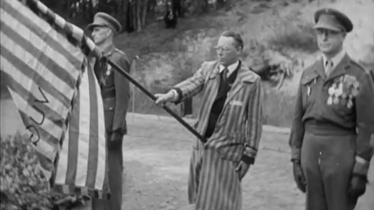 Het laatste beeld van de film toont een ex-gevangene, in kampkleding, met vlag (beeld: History in Color).