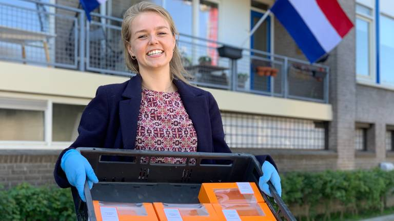 Studente Lisanne van Ree bezorgt oranje tompoucen bij ouderen in Tilburg. (foto: Eva de Schipper)