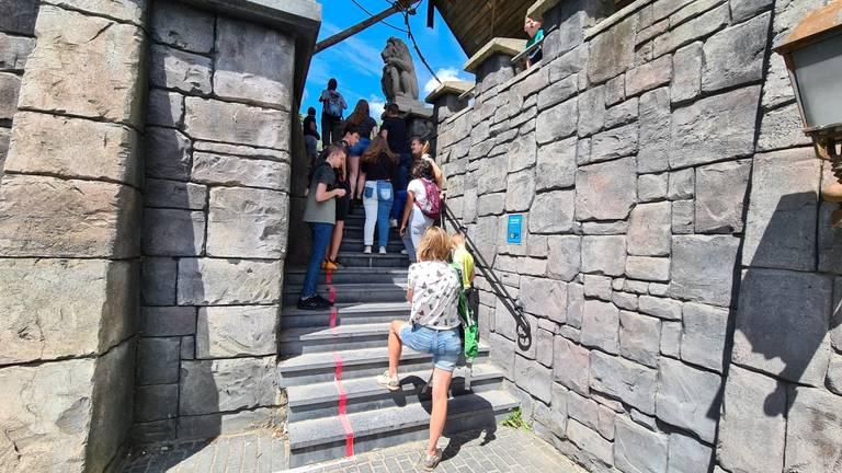 Bezoekers staan massaal op de rode lijnen te wachten.