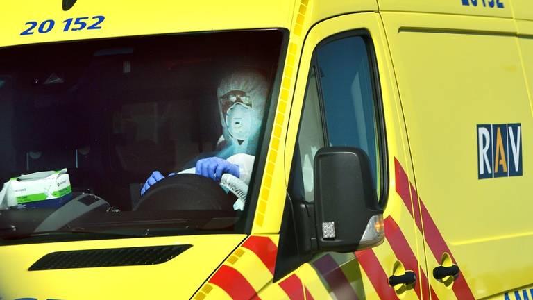 Een volledig tegen het coronavirus ingepakt ambulancechauffeur (archieffoto).