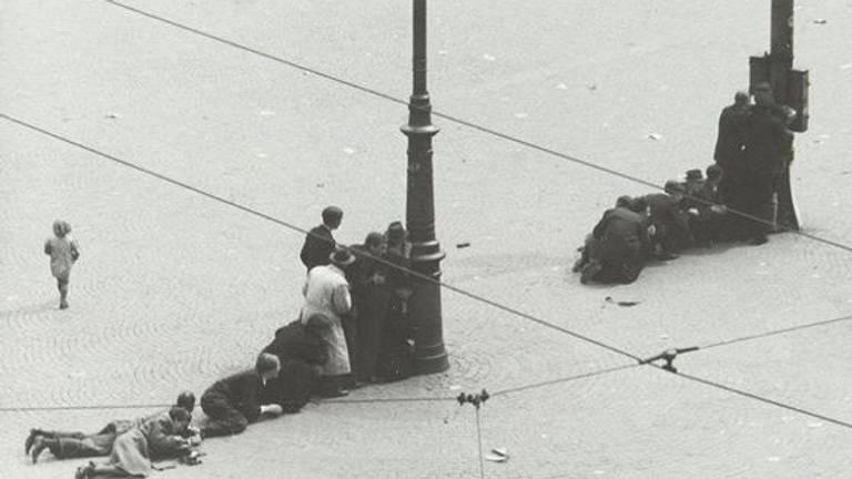 Omstanders zoeken dekking op de Dam (foto: wikipedia)