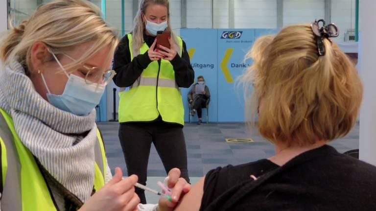 Op verzoek van een verpleegkundige uit Son zet een GGD-medewerkster haar op de foto terwijl ze wordt gevaccineerd (foto: Joris van Duin).