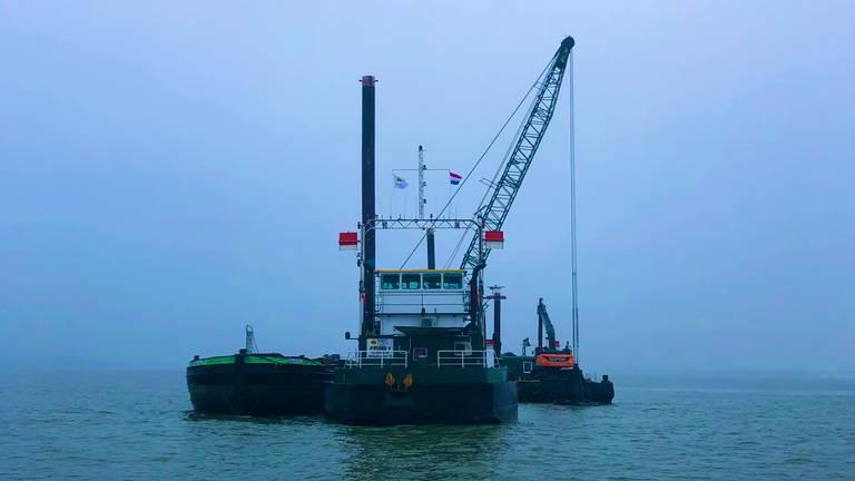 Met een schip en een ponton wordt de oude brandstofleiding opgevist (foto: Raoul Cartens).