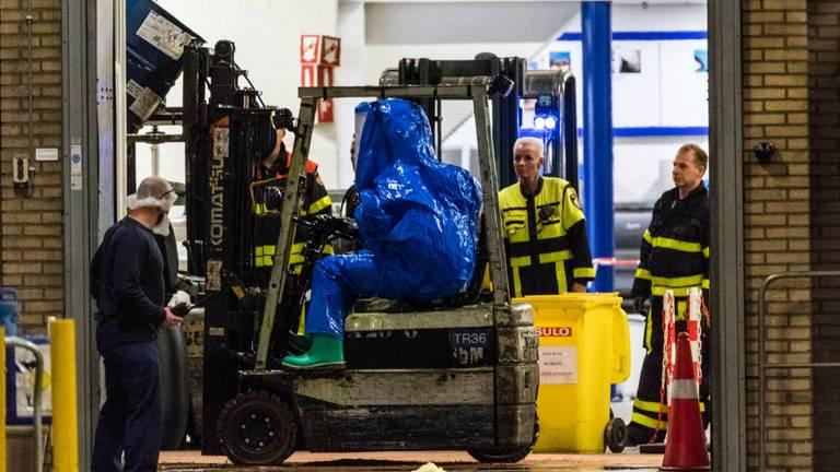 Een man in pak takelt het vat met de chemische vloeistof weg. Foto: Jack Brekelmans/Persburo BMS